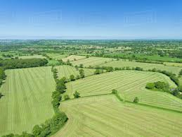 Grass field aerial Large Aerial View Of Summer Grass Silage Fields Farmland And Country Landscape Dissolve Aerial View Of Summer Grass Silage Fields Farmland And Country