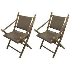 pair of hand stitched leather and faux bamboo campaign folding chairs for