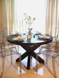 this elegant dining room features a large round wood dining table with clear plastic louis xvi style ghost chairs long neutral ds frame the windows of