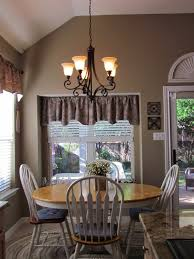 black chandelier by et2 lighting with pedestal dining table and mid century dining chairs plus roman