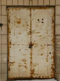 very old beige doors with padlock and myriads of rust spots