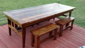 patio farmhouse design with hardwood floor tiles painted with red chalk paint color and large outdoor dining table made from reclaimed wood with bench seat