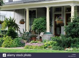 FRONT PORCH OR VERANDA OF 19TH CENTURY AMERICAN HOME OFFERS SHADY SPOT TO  SIT IN THE SUMMER AMID POTTED PLANTS. HOSTA BORDER