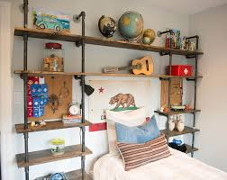eclectic boy s bedroom features an industrial pipe and wood shelving unit which frames the headboard less bed highlighted by a california flag over twin bed