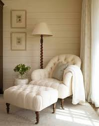Master bedroom chair=Peaceful reading nook with a tufted chair & ottoman,  wood paneled walls, and spiral reading lamp
