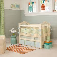 neutral baby bedding set in cream color plus pastel blue skirt and ribbon details with wooden crib in grey white room theme