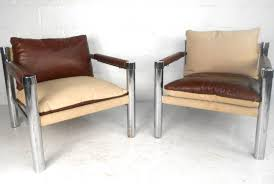this unique pair of matching chairs feature reversible vinyl canvas cushions allowing the piece