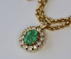 14 carat yellow gold necklace pendant set oval faceted emerald surrounded by brilliant cut diamonds