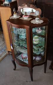 Fashioned from glass and hardwoods, these curio cabinets are ideal for displaying heirlooms, fine china, glassware and other collectibles. Antique Curio Cabinet With Rounded Glass Homes Decoration Ideas
