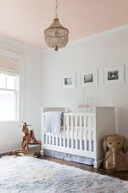 blue and pink nursery features a pink cieling accented with a white beaded chandelier pb kids dahlia chandelier illuminating a white crib fiona crib