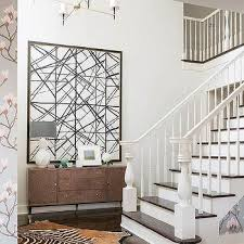 black and white geometric art with brown foyer cabinet