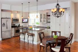 kitchen elegant l shaped eat in kitchen photo in boston with raised panel cabinets white cabinets breakfast table lighting