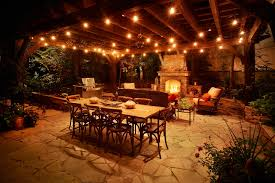 stone floored patio with a set of patio furniture constructed of wooden rectangular table and eight dining chairs beautified by patio light strings