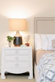 gray linen bed with white nightstand