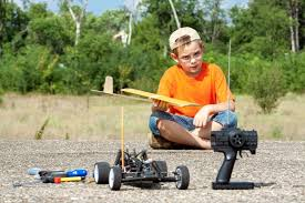 young boy sitting on the ground playing with remote controlled car