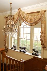 one large fringed scarf dd on each corner of a wooden decorator pole topped with rosettes valance curtainshanging