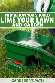 lime pellets being added into a push spreader on a grassy lawn