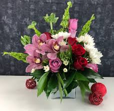 a white square vase filled with roses cymbidium orchids mums and bells
