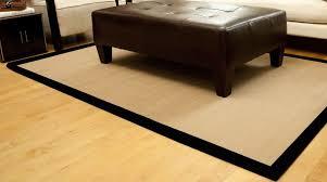 dark brown ottoman sitting a top a khaki brown sisal rug with black border