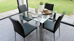 small glass kitchen dining table and black dining chairs