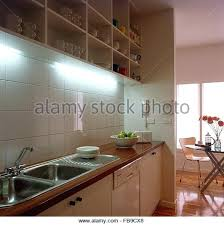 kitchen down lighting. Kitchen Down Lighting Above Double Stainless Steel Sinks In Modern With Open Shelving Stock Image Ideas Lowes M