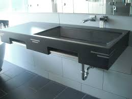 bathroom rectangle black concrete sink and steel faucet on white tiles bathroom wall