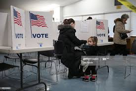 Primary day voter Amanda Binette fills out her ballot as her ...