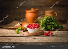 raspberries in a wooden dish on the table rustic style decoration clay pots and bowls photo by besedinajulia