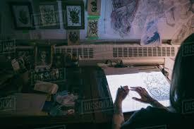 artist office. Tattoo Artist Sketching On Light Table In Dark Studio Office