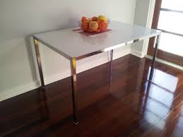 stainless steel coffee table with frosted glass and varnished wood floor plus white wall paint home design