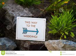 sign reads this way to the wedding at an outdoor venue in southern oregon