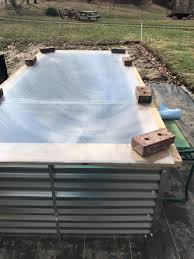 side shot of a galvanized steel raised bed with a greenhouse panel laid over top
