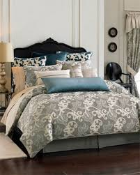 a creamy bedroom with a navy velvet bed grey and blue bedding with prints