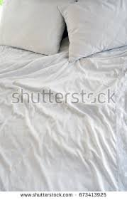 white bed sheets background. Crumpled White Sheets And Pillows, Morning Bed Kept Warmly Bodies. Background Creased Cloth