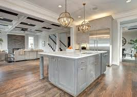 kitchen with stained gray cabinets and carrara marble countertops with gold globe pendant lights