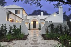 Stunning 2-story white stucco modern home accented with a gray shingled  roof boasts a
