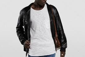 indoor portrait of attractive young african male model dressed casually posing in studio stylish dark skinned student wearing leather jacket and shoulder