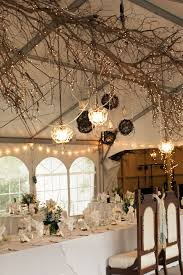rustic indoor wedding decoration with tree braches and lights