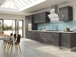 grey varnished wood kitchen cabinet blue glass kitchen backsplash stainless steel wall amount range hood grey