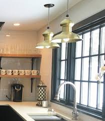 i chose these raw brass pendants because a black and white kitchen with too much stainless would look too contemporary for the house sarah explains