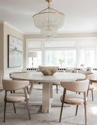 round gray oak dining table with cream leather dining chairs