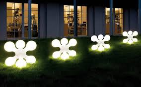 unusual shape of contemporary outdoor lighting fixtures with bright lighting on green grass yard