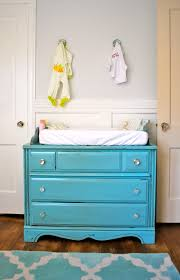 blue distressed wooden changing table dresser for nursery having three drawers and round knobs plus blue patterned carpet accent