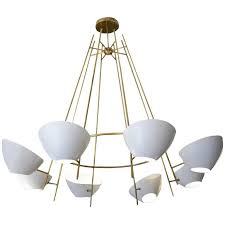 round brass chandelier with white cups for