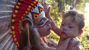 portrait of attractive indian woman in native american indian headdress with bright makeup nursing her cute son autumn forest