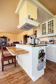 A Small Kitchen Split Between Light Hardwood Floors And Dusky Red Tile. The  Two