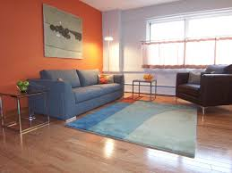 contemporary living room with orange accent wall grey walls and charcoal grey sofa design within reach