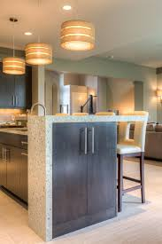 a unique kitchen island paninsula with bar stool seating featuring gray stained dura supreme cabinetry