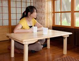 A woman sitting cross-legged at a table