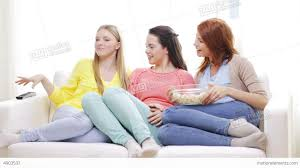 watching tv at home. three smiling teenage girls watching tv at home stock video footage